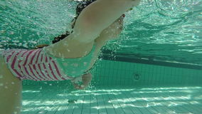 Slow motion of young girl swimming underwater with goggles stock video footage