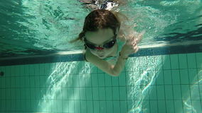 Slow motion of young girl swimming underwater and making somersault stock footage