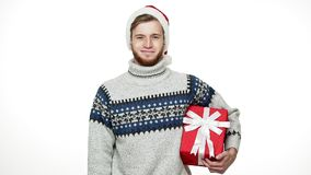 Slow-motion young handsome man holding present and smile to camera on Christmas day. Slow-motion young handsome man holding present and smile to camera on stock video footage