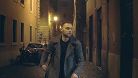 Slow motion. Young handsome man walking through the deserted street with lights in the evening alone.
