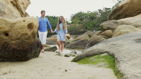 Slow motion Young happy beautiful couple of lovers, in blue clothes, holding hands, walking along the seashore, talking stock footage