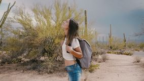 Slow motion young happy caucasian tourist woman looking around enjoying amazing hike at cactus desert national park.