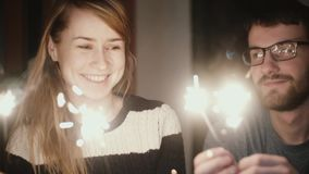 Slow motion. Young happy couple sitting at home in the evening and holding the sparklers, enjoying time together. stock video footage