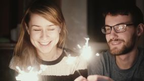 Slow motion. Young happy couple sitting at home in the evening and holding the sparklers, kissing each others.