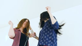 Slow motion of young happy women friends dancing over a bed with earphones and have fun stock footage