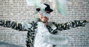 Slow motion of young hipster dancing on brick background when money falling