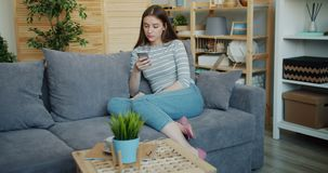 Slow motion of young lady with serious face using smartphone at home on couch stock footage