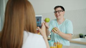 Slow motion of man juggling apples while woman taking photo with smartphone. Slow motion of young man juggling apples having fun in kitchen while woman is taking stock footage