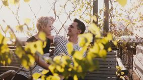 Slow motion young man and woman sitting together on a park bench on beautiful sunny autumn day, having fun and smiling. Slow motion young man and woman sitting stock footage
