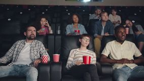 Slow motion of young people yawning watching boring film in cinema stock video footage