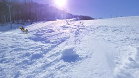 SLOW MOTION: Young pro snowboarder riding the half pipe in big mountain snow park, spraying snow into camera on halfpipe stock video footage