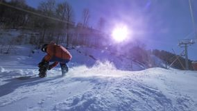 SLOW MOTION: Young pro snowboarder riding the half pipe in big mountain snow park, spraying snow into camera on halfpipe stock video