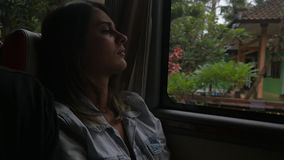 Slow motion of a young sad woman traveling by bus. Pretty young woman travels by car and looking out the window and enjoying the view of beautiful tropical stock footage