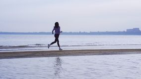 Slow motion: young slim brunette woman in sports uniform runs along the sandy shore on a summer morning stock video footage