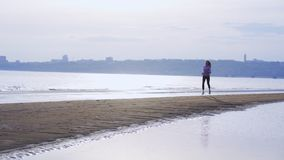 SLOW MOTION: Young slim brunette woman in sports uniform runs along the sandy shore on a summer morning. stock video footage