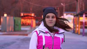 Slow motion: young slim girl in a sports hat and blazer makes a run on the concrete path in the morning. In the first rays of the rising autumn sun stock footage