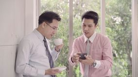 Slow motion - Young smiling men enjoying drinking warm coffee standing while relax in office. Asian business man using smartphone. stock video
