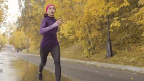 Young sportswoman running along the road. Slow motion of young sportswoman running along the road. Dolly shot stock video
