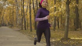 Young sportswoman running along the road. Slow motion of young sportswoman running along the road. Dolly shot stock video footage