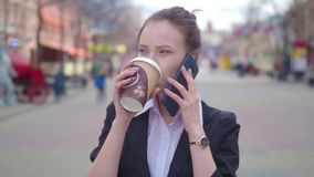 Slow Motion Young successful businesswoman using smart phone in city downtown, professional female employer talking with. Business partner drinking coffee stock footage