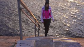 Slow motion: a young woman in a blazer and sweatpants comes down the stairs to the water of a large lak. E in the morning at the first rays of dawn stock video footage