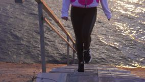Slow motion: a young woman in a blazer and sweatpants comes down the stairs to the water of a large lak. E in the morning at the first rays of dawn stock footage