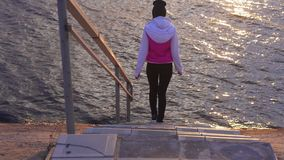 Slow motion: a young woman in a blazer and sweatpants comes down the stairs to the water of a large lake. In the morning at the first rays of dawn stock footage