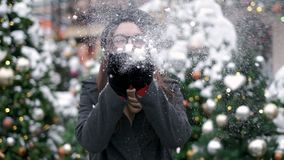 SLOW MOTION: Young woman blowing snow. Young woman blowing snow. Portrait of cute young woman blowing on snow in her stock footage
