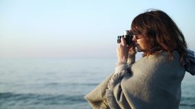 Slow motion of young woman in grey clothes taking pictures of ocean stock video