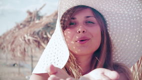 Slow motion young woman in a hat sends an air kiss to her beloved on the beach