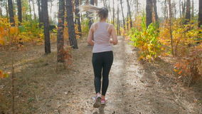 Slow motion of young woman running in pine forest at morning stock footage
