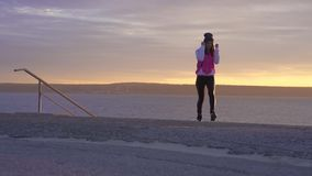 SLOW MOTION: A young woman in a sports hat, sports jacket and sneakers makes a morning warm-up on the embankment of a large river stock video footage
