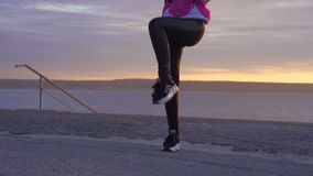 Slow motion: a young woman in a sports hat, sports jacket and sneakers makes a morning warm-up on the embankment of a large river stock footage