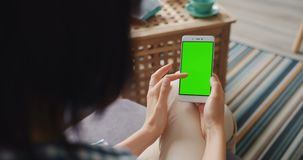 Slow motion of young woman touching smartphone with green screen at home. Slow motion of young woman touching smartphone with green mock-up screen at home using stock video footage