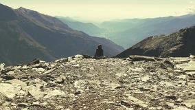 Slow motion zoom to lonely woman sitting on rocky terrain and watching the expansive view over the valley. stock video footage