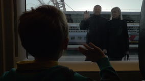 Slow motionview of boy watching in window from rail train and saying goodbye his grandparents, swinging arms stock video