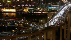 Slow moving cars on overpass interchange,Brightly lit urban building,shanghai. Aerial freeway busy city rush hour heavy traffic jam highway Shanghai at night stock video footage