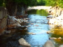 Slow moving water through mountain stream. Miniature effect rocky riverbed in forest with dappled sunlight and defocused foreground and background Stock Photos