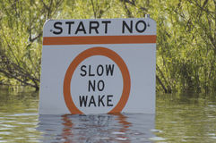 Slow-No-Wake. A slow-no-wake sign is becoming submerged during spring flooding Stock Photos