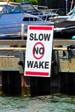 A slow no wake sign on a dock with boats in the background.  royalty free stock photography
