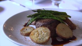 Slow pan down to a thick steak in a restaurant stock video footage
