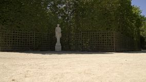 Slow pan shot in gardens of Versailles with bushes and statues all around. Slow low angle pan shot of gardens of Versailles in France at spring time at daylight stock footage