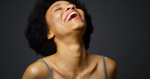 Slow pan up casual black woman laughing and smiling. In front of black background Royalty Free Stock Photos