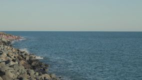 Slow panorama of rocky sea shore with beach and tourists. Wide shot stock video footage