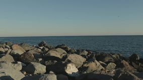 Slow panorama of rocky sea shore with beach and tourists. stock video footage