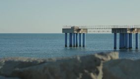 Slow panorama of sea pier with blurry rocky shore on the foreground. stock video