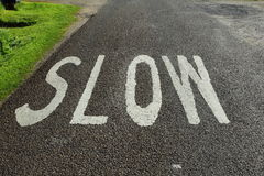 Slow. Public road with SLOW sign warning Stock Photos
