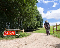 Slow. A rambler walks slowly along a path on a summer day Royalty Free Stock Image