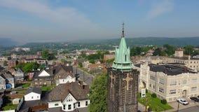 Slow reverse aerial establishing shot of church in small town  USA. A slow reverse aerial establishing shot of a church steeple in a small town's business stock video footage