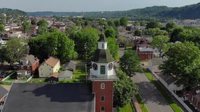 Slow reverse aerial view of small town's church steeple. A slow reverse aerial view of a small town's church steeple and clocktower. Pittsburgh suburbs stock footage
